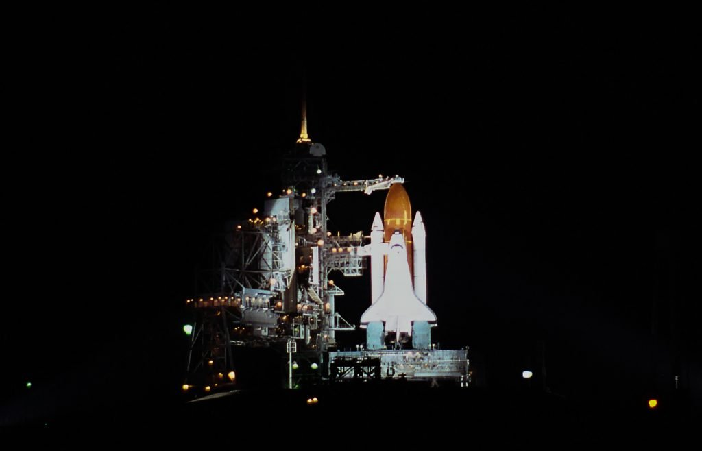 space shuttle on launchpad at night